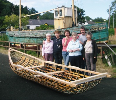 Members of Inishowen cancer Group Éist and boat builder Dónal MacPolin, with the skeleton of their currach before it was finished.